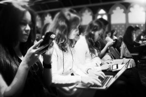 Female journalists seated at a news event, with one gathering information on her phone, another on her laptop, and a third on a tablet. Other women are seen in the background, but not in clear detail.