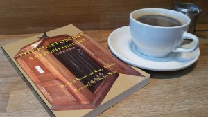 """A book titled """"The Kinetoscope: A British History"""" is placed beside a cup of tea. The book's cover features a kinetoscope, with the film winding it's way through."""
