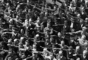 Historical photo of a group of men performing the Nazi salute in Nazi Germany. One person is refusing to do so and standing with his arms crossed.