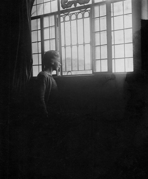 Fotografía en blanco y negro de Alfonsina Storni mirando por unas ventanas grandes y llenas de luz