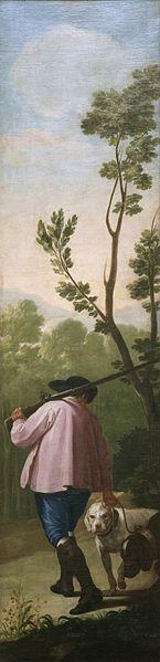 Un cuadro vertical de un cazador de espaldas caminando con dos perros, con arboles al fondo