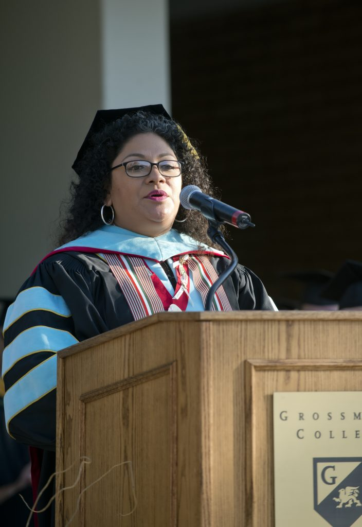 Pearl Lopez in cap and gown behind podium giving commencement speech at Grossmont College
