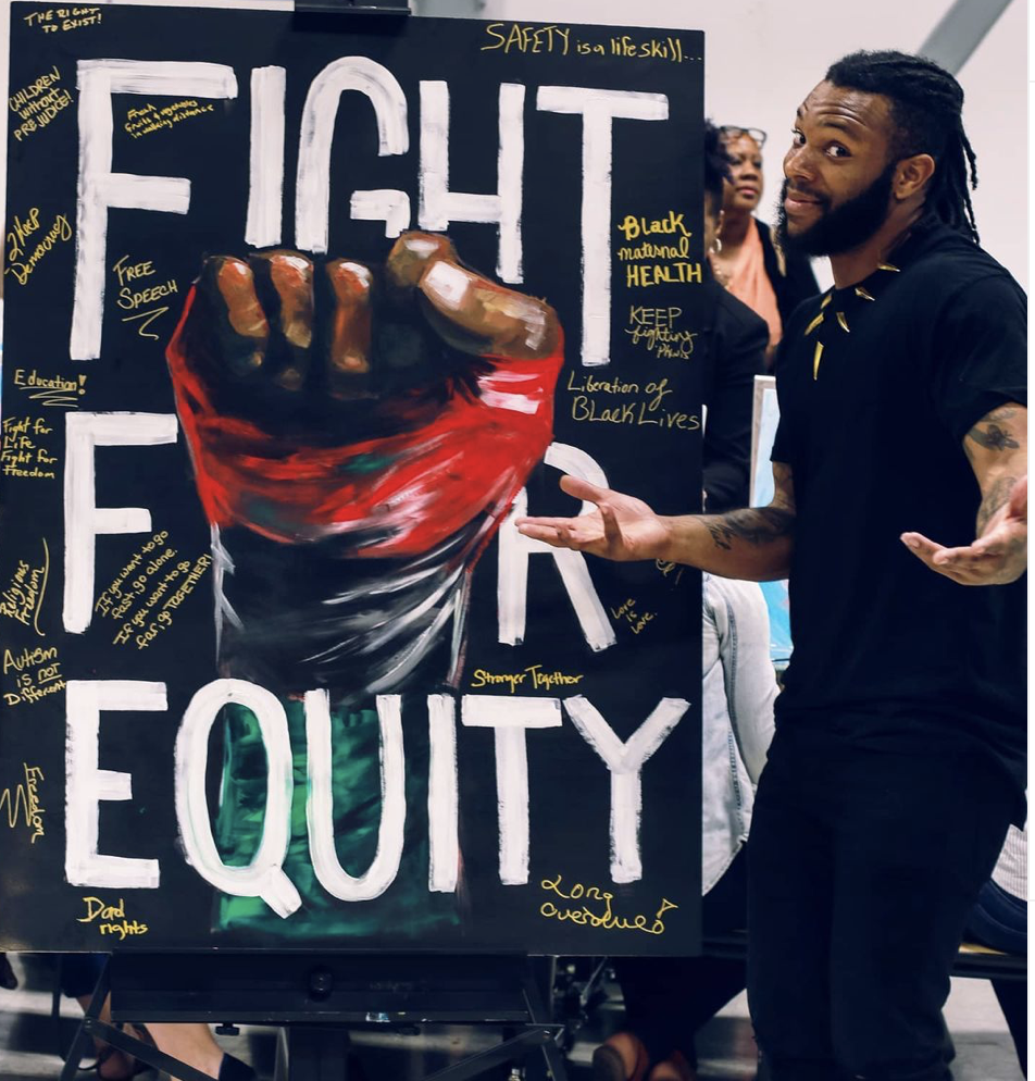Often the story is equality but that leaves the system unbalanced when equity can bring things closer together. For this community event, I painted the fist and main text. The rest of the painting is filled in with words from people in the community stating what things we should fight for and why