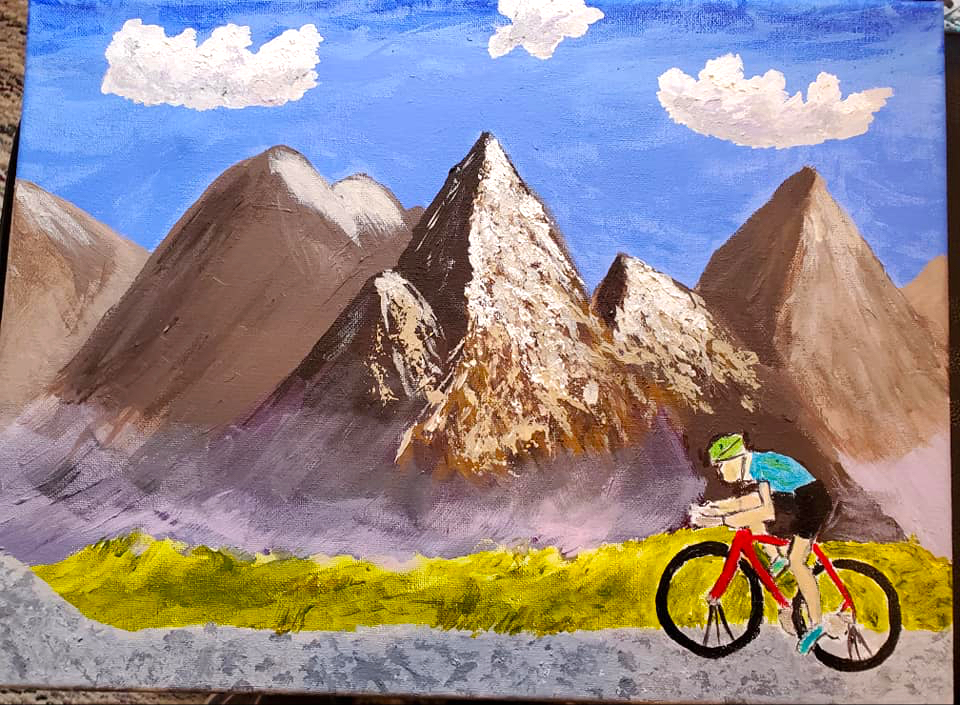 A bicyclist rides across a rugged landscape in front of ragged mountains with clouds high above in the blue sky