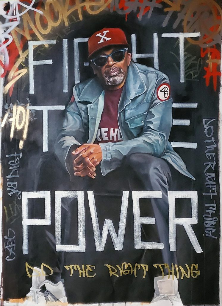 """Legendary filmmaker and culture crafter, Spike Lee sits in a """"X"""" and Morehouse college t-shirt in front of the words of the iconic song """"Fight the Power"""". Spike Lee has always pushed the limits of storytelling and telling the truth of what goes on under the American sun in its relation to Blackness and race in general. The graffiti is used to express the urban grit it takes to push the limits of any art form"""